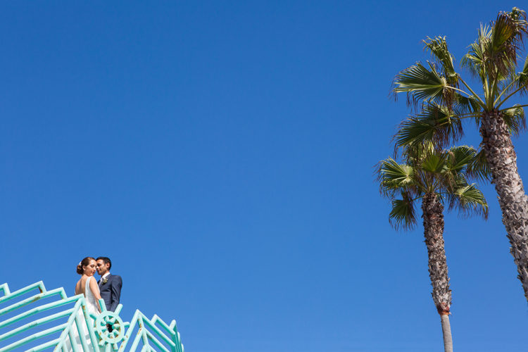 A bride and groom on a look out at Manhattan Beach in Los Angeles against a brilliant blue sky. Photo taken by destination wedding photographer - Mala Photography