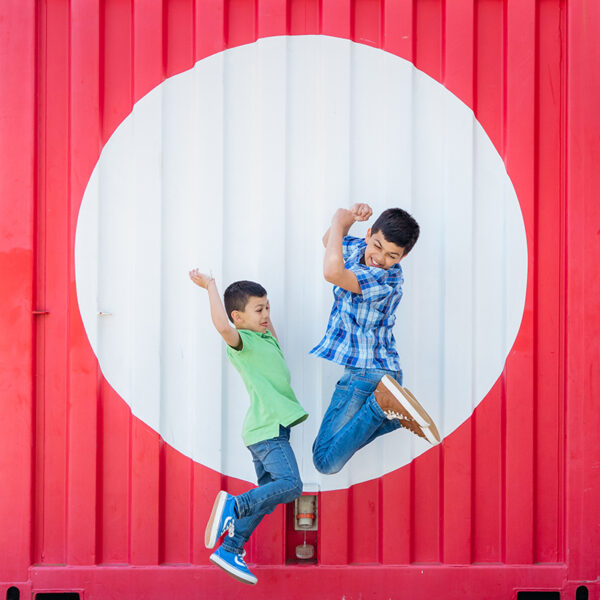 This is a fun, lively, vibrant and contemporary portrait of two boys. They are jumping up in the air in front of a red shipping container with a large red spot on it. The boys are jumping with their arms and legs up in the air with big smiles on their faces.