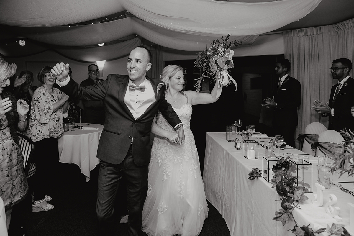 A Bride and Groom entering their wedding reception at Castaways Resort in Waiuku, New Zealand. Photography by Auckland based wedding photographer, Mala Photography.