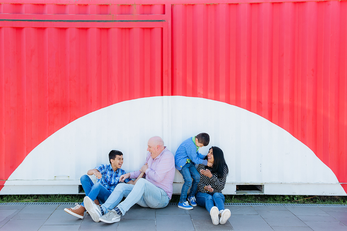 This is a colourful and contemporary family photo taken by Auckland based family photographer - Mala Photography. This is a photo of a family of four sitting in front of a big, red and white shipping container. The family are playing and having fun together. They are laughing and having fun.