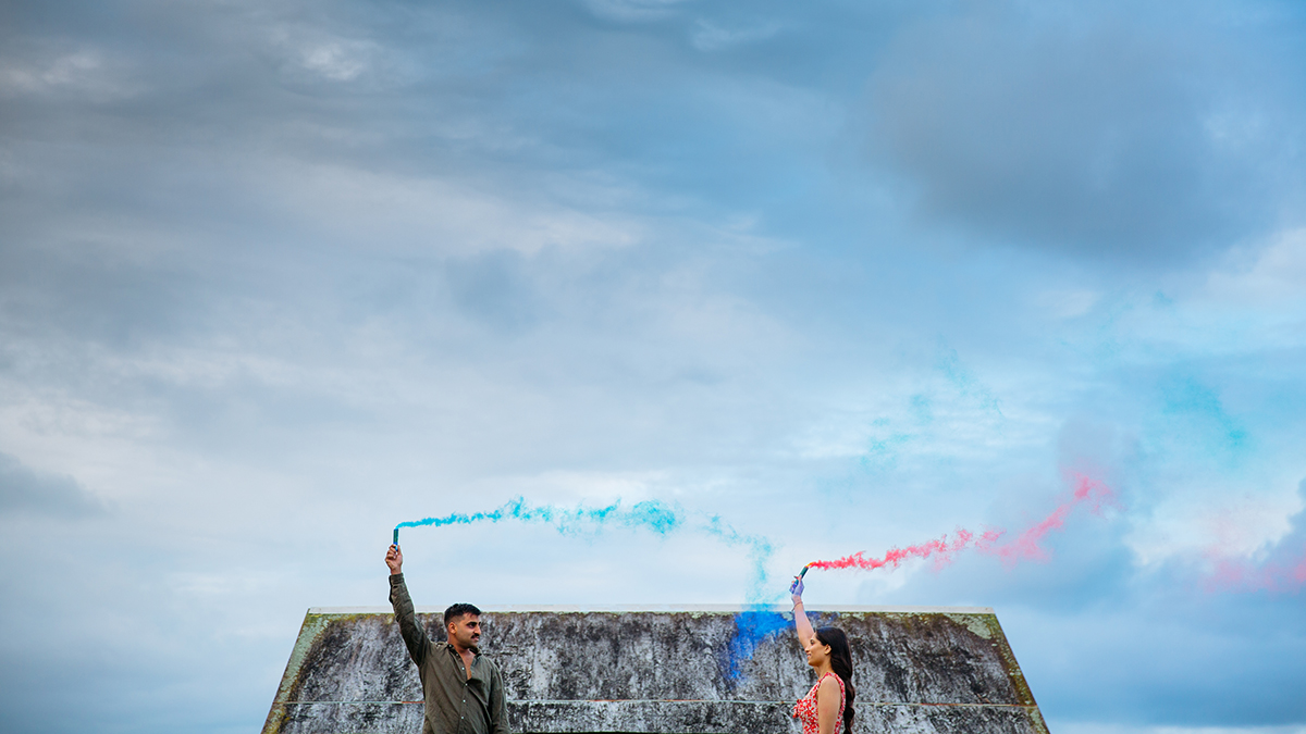 This is a photo of a couple taken during their engagement shoot by Mala Photography, an Auckland based wedding and engagement photographer. The couple are standing facing each other a couple of meters apart. They are standing in front of a wooden structure holding coloured smoke bombs. The guy is holding a blue smoke bomb and the girl is holding a red one.