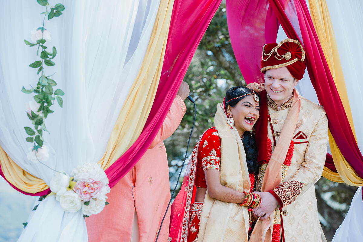 A wedding photo from a stunning fusion Indian wedding at Thomas's Bach on Waiheke Island in New Zealand. The mandap(ceremonial area) was set up outside with a stunning view int the background. Indian weddings are beautiful, bold and vibrant.. Photography by Mala Photography from Auckland.