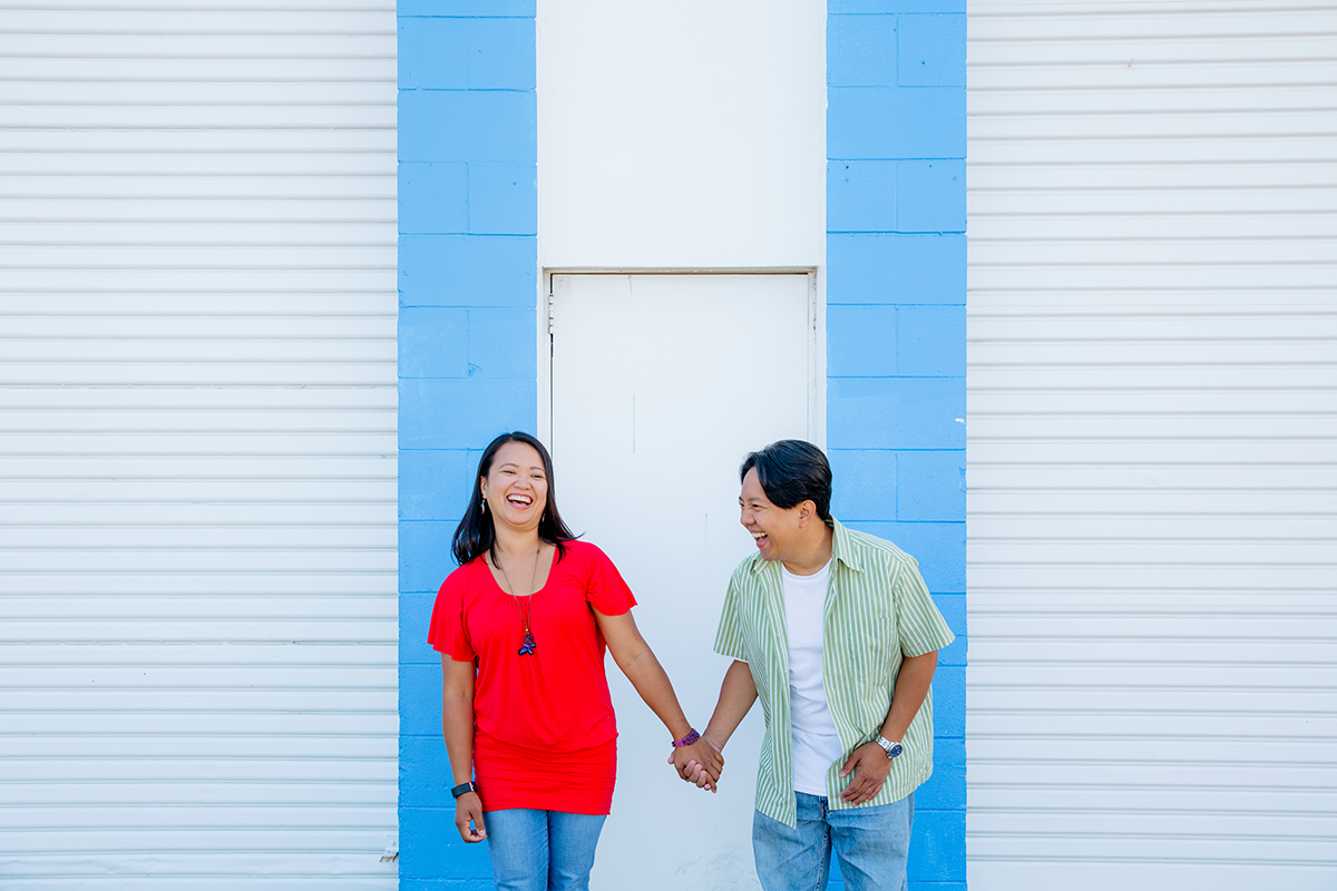 Auckland wedding and engagement photographer Mala Photography took this photo during this couple's engagement shoot. This is a photo of a couple holding hands and laughing hysterically. They are standing in front of a blue and white background.