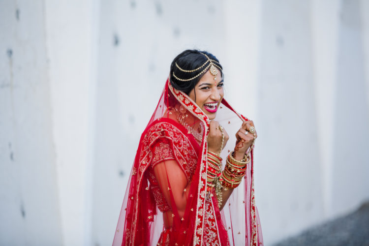 This is a photo of an Indian Bride in traditional wedding attire on her wedding day. She is laughing and looking happy and full of joy. She looks stunning in red in this candid shot taken by Auckland wedding photographer Mala Photography.