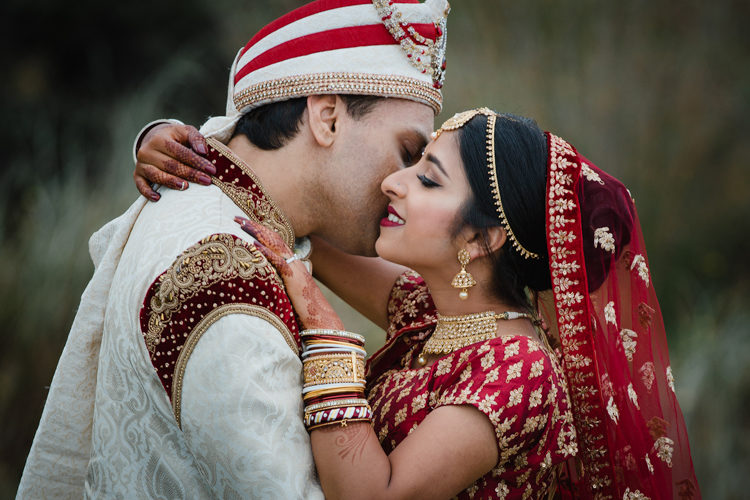 A wedding photo taken at a traditional Indian wedding of a Bride and Groom holding each other affectionately. They are both dressed in traditional Indian wedding attire featured red and gold. This wedding photo was taken by Mala Photography, a wedding photographer in Auckland that has photographed a lot of Indian weddings.