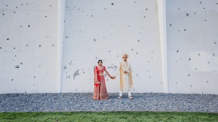 A wedding photo taken at a traditional Indian wedding of a Bride and Groom holding hands affectionately. They are both dressed in traditional Indian wedding attire featured red and gold. This wedding photo was taken by Mala Photography, a wedding photographer in Auckland that has photographed a lot of Indian weddings.
