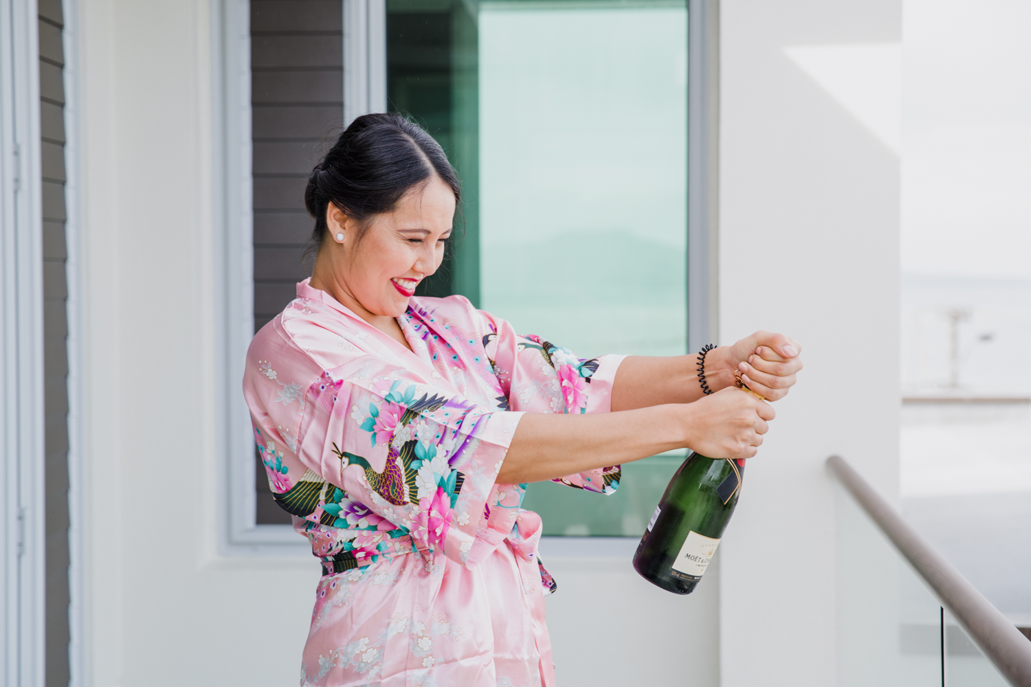 Bride's maid cracking open a bottle of bubbles. This image was taken by Mala Photography, an Auckland based wedding photographer. The wedding was at Markovina Vineyard Estate In Kumeu, Auckland.