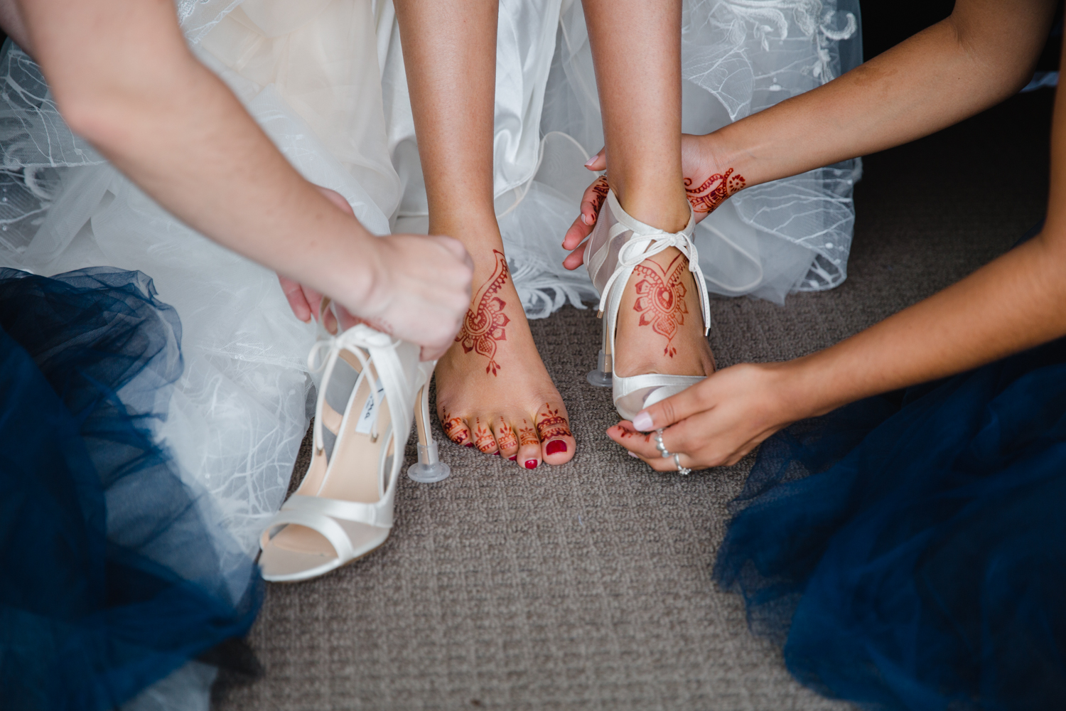 An artistic image of a Bride having her shoes put on by her bride's maids. The Bride's henna is shown beautifully in this image as well. This image was taken by Mala Photography, an Auckland based wedding photographer. The wedding was at Markovina Vineyard Estate In Kumeu, Auckland.