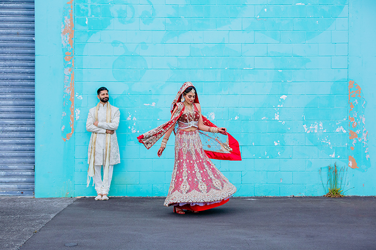 This is a photo of an Indian Bride dressed traditionally. She is spinning around while her husband watches her smiling. He is dressed traditionally too in a gold Indian suit. The Bride's outfit is bright red with lots of bling. As she spins the fabric swishes around her beautifully. This is a photo from an Indian wedding in Auckland by Mala Photography.