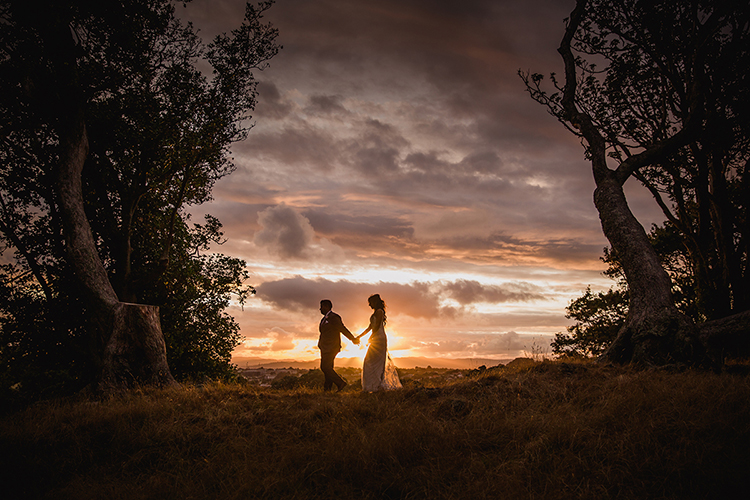 Taken by Mala Photography, and Auckland based wedding and engagement photographer. This is a photo taken at sunset of a Bride and Groom walking across a hill top through long grass with trees on either side of them. The Groom is leading the Bride. The image is dark and moody with a warm, dramatic sky.
