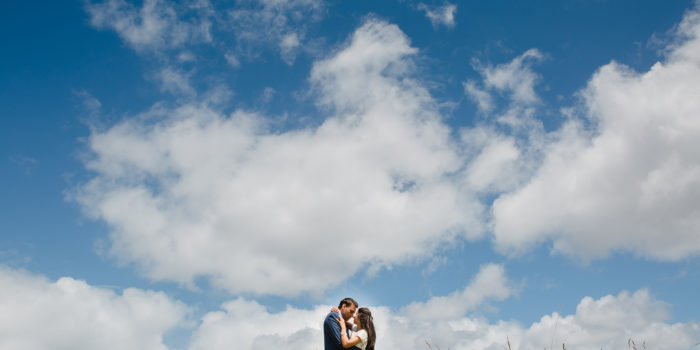 A wedding photo from a traditional Indian wedding. The photo is of an Indian Bride and Groom on top of a mountain. They are holding each other. Photo credit - Mala Photography