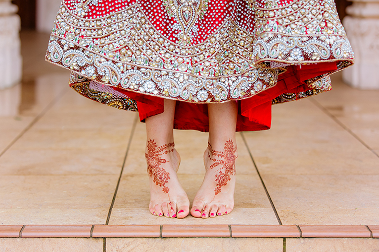 This photo is of an Indian Bride's feet. They are adorned with bridal henna. She is standing on the steps of the temple where she just got married. The Bride is holding up her long skirt so feet and henna can be seen. This is a creative shot taken by Auckland based Indian wedding photographer Mala Photography.