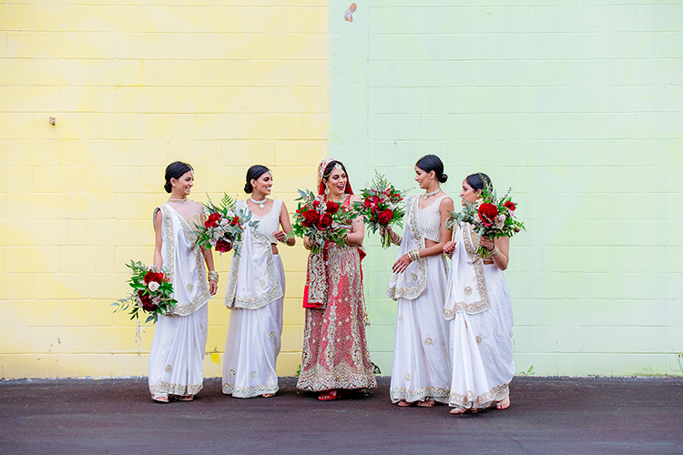 An Indian Bride and her bridesmaids are talking candidly and laughing. They are dressed traditionally with the Bride in a red wedding outfit and the bridesmaids in white. They are holding their bouquets and are standing in front of a yellow and green wall. This is a striking, colourful image by Mala Photography, an Auckland based wedding photographer.