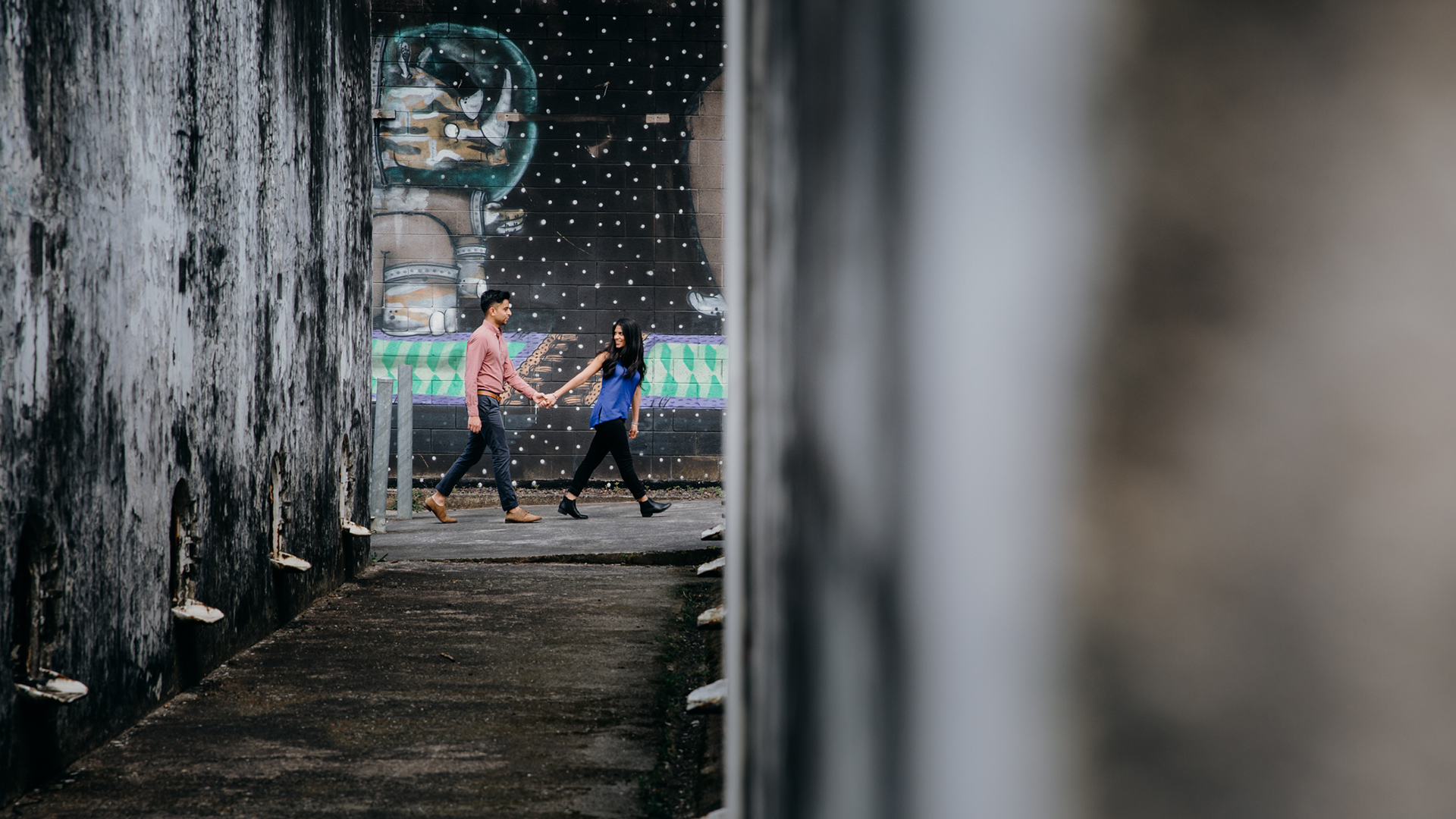 A creative, contemporary photo of a couple taken during their engagement shoot. They are holding each others hand as they walk passed a mural. This photo was taken by Mala Photography, a photographer in Auckland that specialises in engagement and wedding photography.