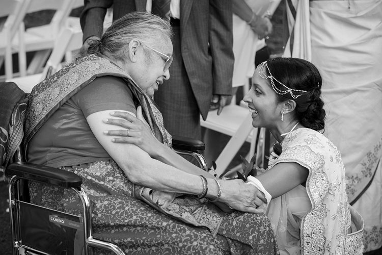 A black and white wedding photo taken of a bride being congratulated by her grandmother at the Royal Auckland Golf Club. It is a precious moment captured by Mala Photography, an Auckland based wedding photographer.