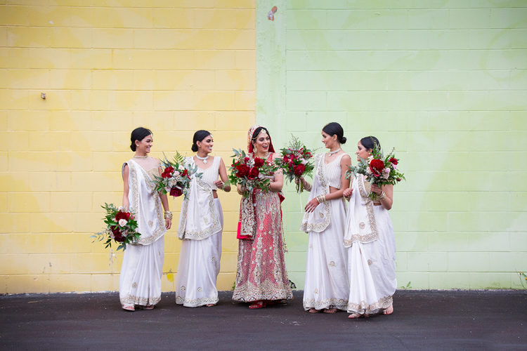 A wedding photo taken at a traditional Indian wedding of a Bride and her bridesmaids laughing and having fun. They are both dressed in traditional Indian wedding attire featured red and gold. This wedding photo was taken by Mala Photography, a wedding photographer in Auckland that has photographed a lot of Indian weddings.