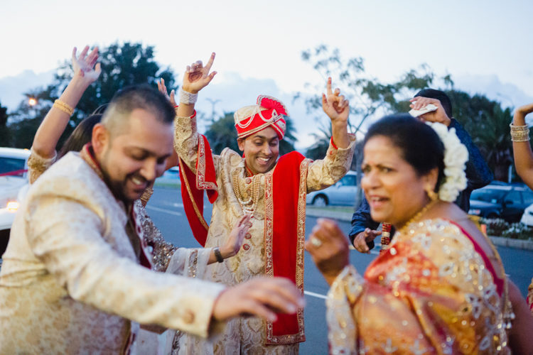 A photo of traditional Indian dancing at an Indian wedding. Photo taken by Mala Photography.