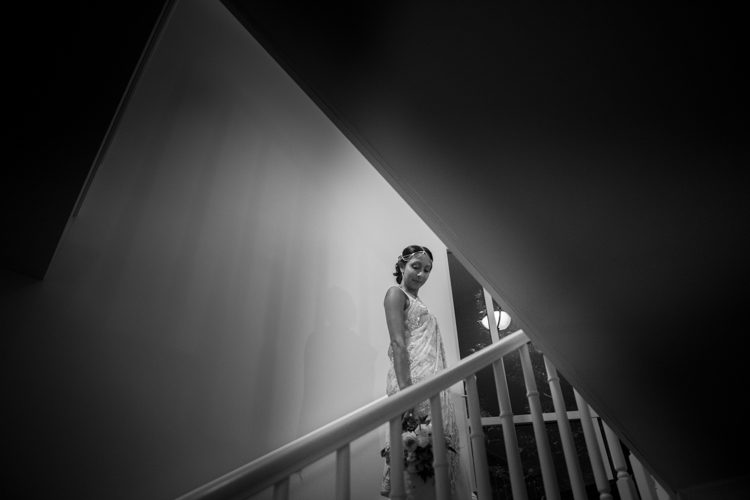 A wedding photo of a Bride taken on the stairs at the Royal Auckland Golf Club in Auckland, New Zealand. Photo taken by Mala Photography, and Auckland based wedding photographer.