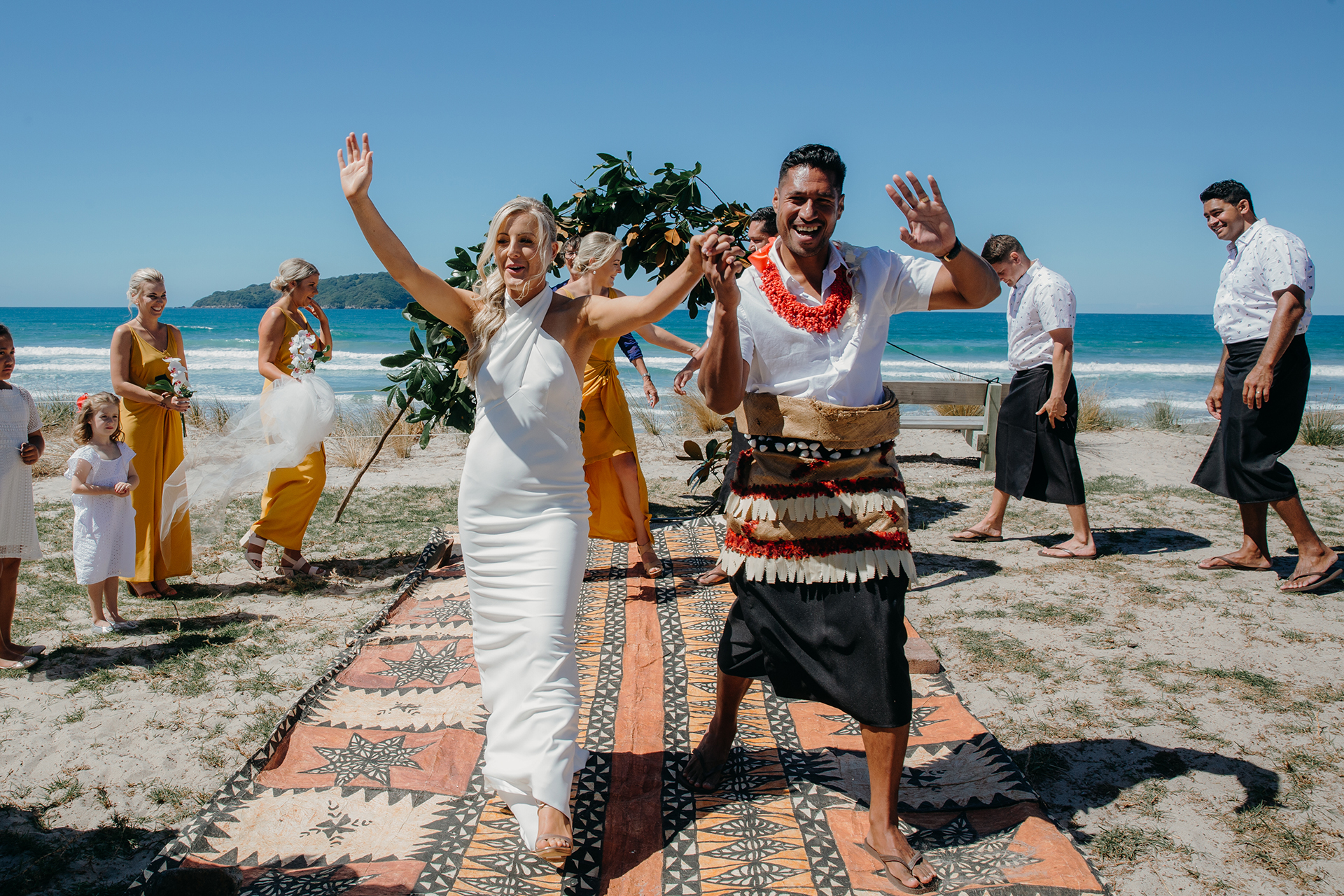 A stunning photo of a Bride and Groom who have just been announced as husband and wife. Their wedding ceremony was at Pauanui Beach, Coromandel in New Zealand. Their wedding photographer was Mala Photography from Auckland.