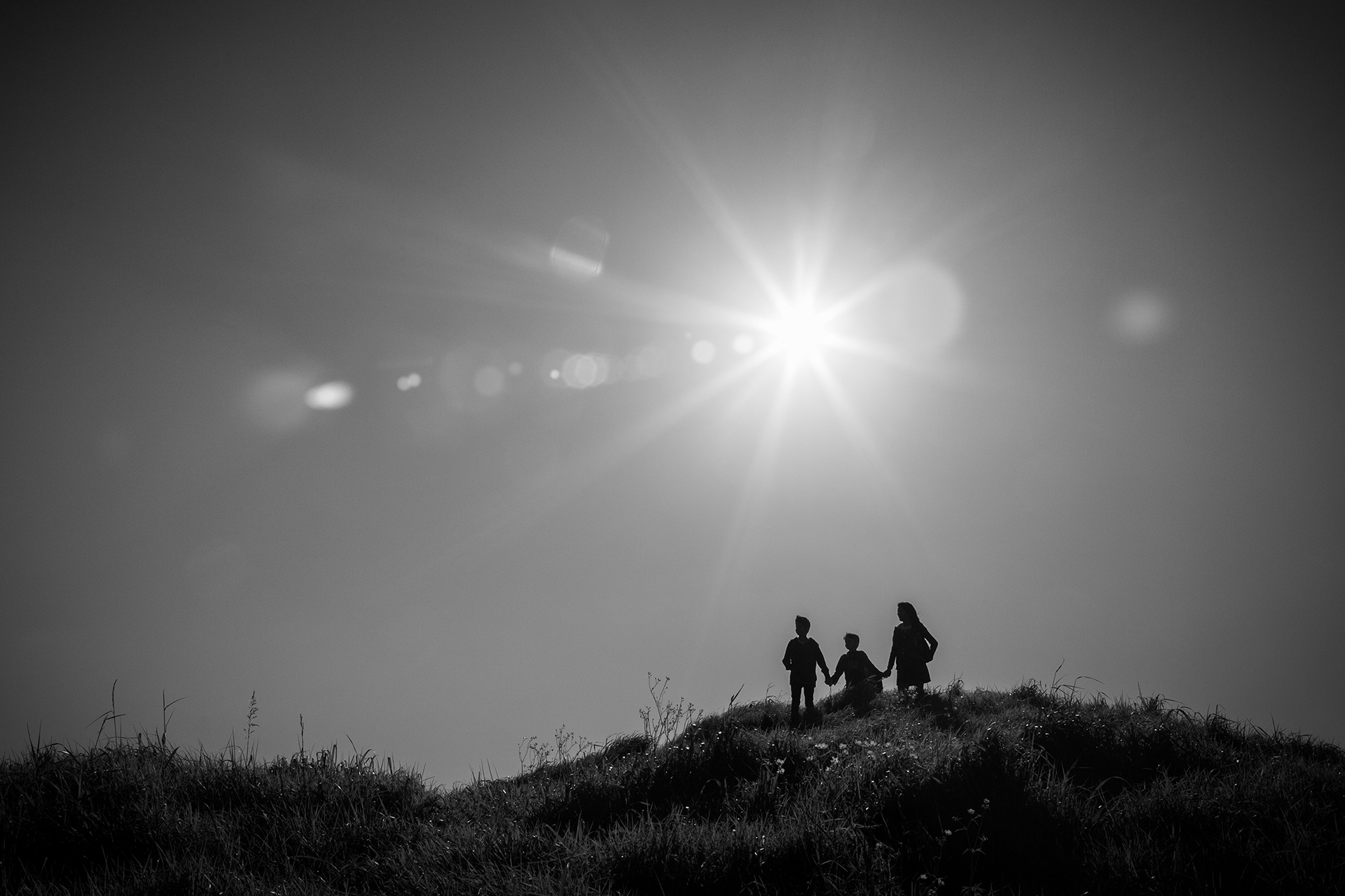 A silhouette of three children standing on a hill looking out together in the same direction. The children are holding hands so they look close and connected. The sun appears as a star burst with flare. This photo was taken by Mala Photography, and Auckland based family portrait photographer.