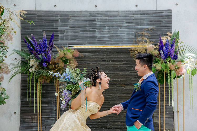 This is a photo from a sustainable styled wedding shoot by Mala Photography. an Auckland based wedding photographer. This photo was taken at Cocoon House, an upmarket, boutique style wedding venue in Auckland. In this photo an untraditionally dressed Bride and Groom are holding hands, looking at each other and laughing their heads off. They are happy and joyful on their wedding day during their wedding ceremony at Cocoon House.