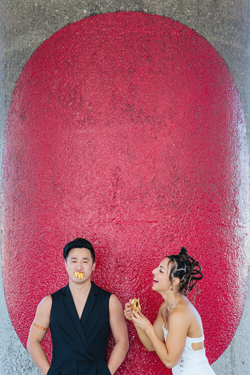 This is a wedding photo taken by Mala from Mala Photography in Auckland. This photo is of a Bride and Groom eating burgers and fries on their wedding day. They are standing in front of a giant red spot painted on a column.