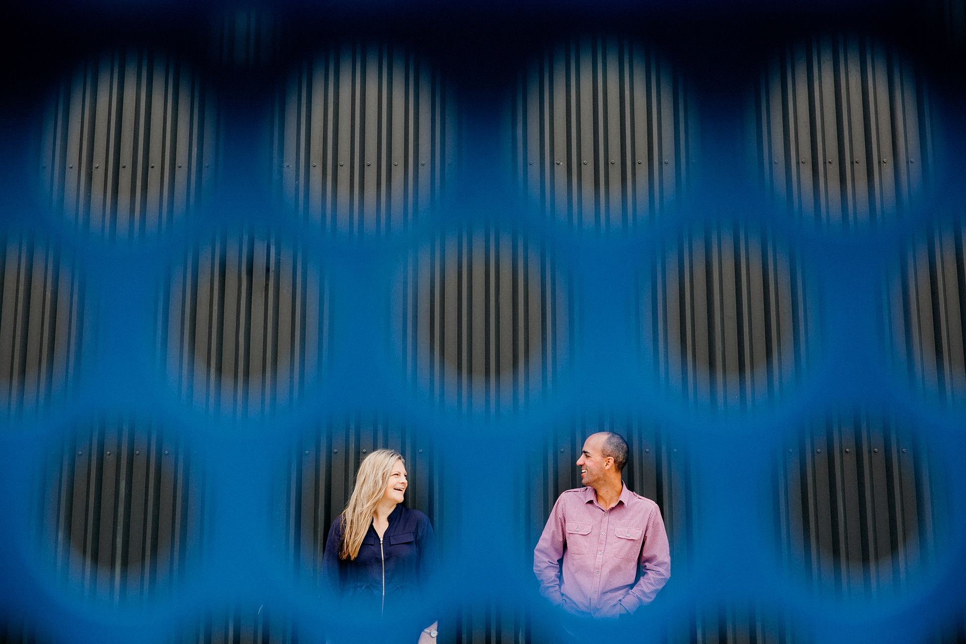 This is a photo taken during an engagement shoot by Mala Photography, an Auckland based engagement and wedding photographer. This photo is of a newly engaged couple looking at each other lovingly and smiling. Mala has photographed them through a milk tray, using the round holes in the tray to frame the couple.