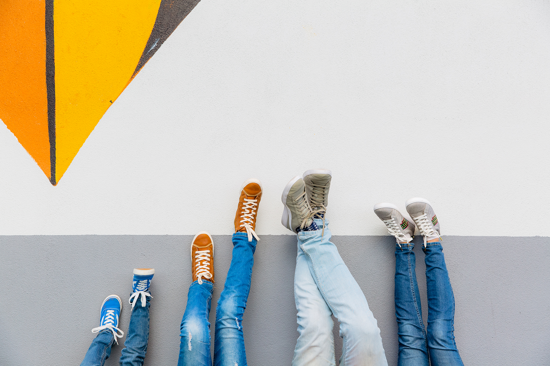 This is a contemporary and quirky family portrait by Auckland based photographer - Mala Photography. This is a photo of a families legs, feet and sneakers against a wall. This is a family of four ie parents and two kids. They're all wearing blue denim jeans and sneakers in different colours.