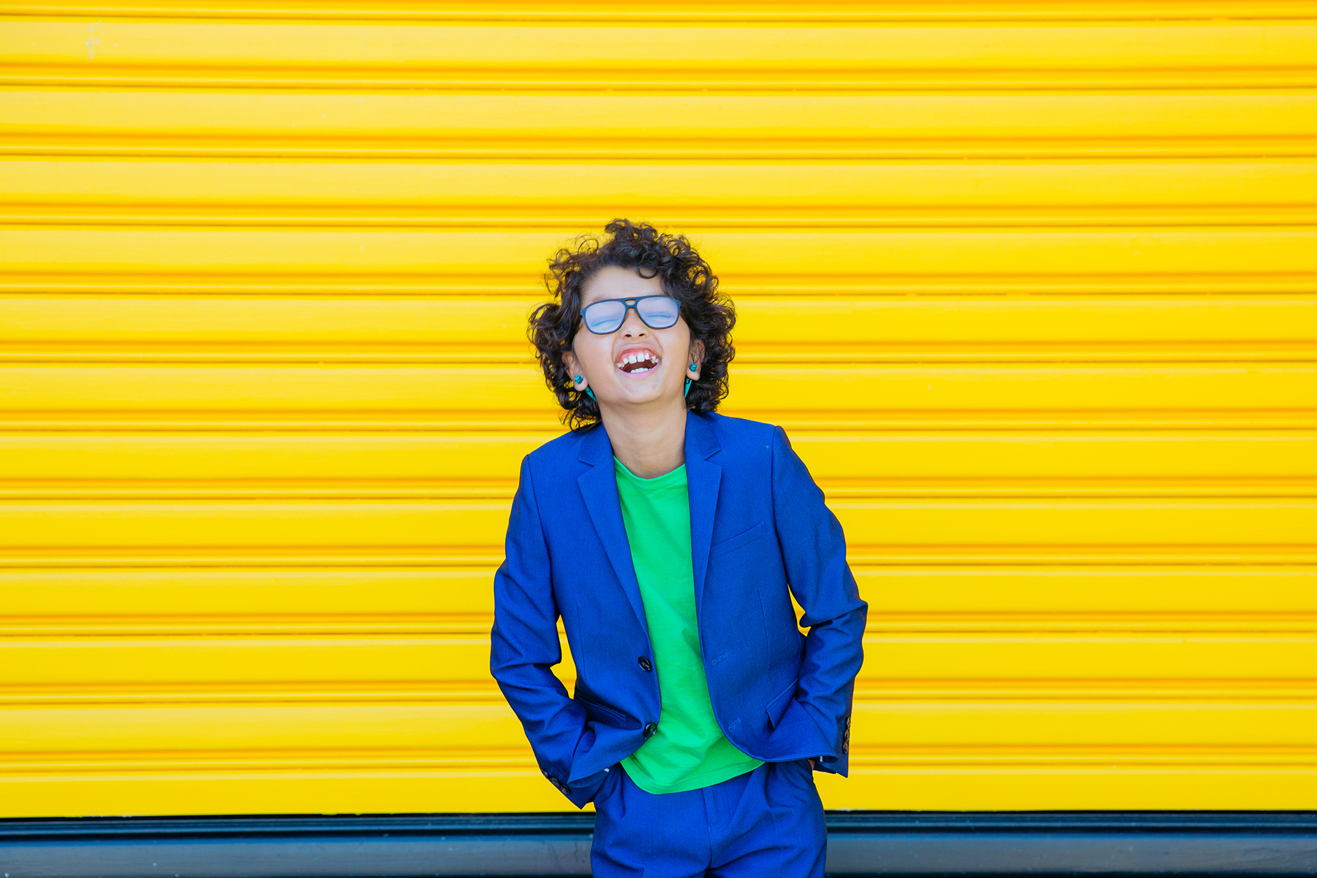 This is a portrait of a young boy taken my Auckland based photographer Mala Photography. The boys is dressed in a blue suit with a green t-shirt. The boy has long, curly hair, is wearing glasses and earrings. He has his hands in his pockets and looks very cool and stylish. He is laughing hysterically with his head up and eyes closed. The image is striking as the boy is standing in front of a bright, yellow roller door.