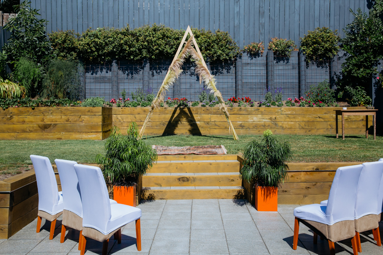 A photo taken by Auckland Wedding Photographer - Mala Photography. A photo of a backyard in Auckland set up for a wedding ceremony. The arch is a triangle with toi tois attached to it.