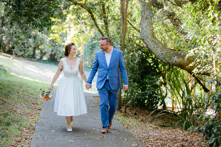 Mala Photography, a wedding photographer based in Auckland took this photo of a couple on their wedding day. They are walking on a path in a park, looking at each other, smiling and are hand in hand.