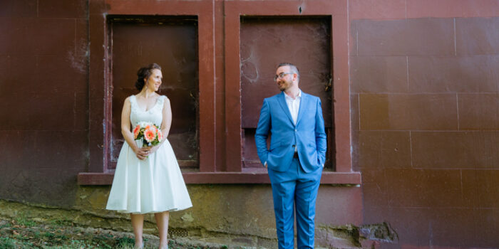 Auckland Wedding Photography by Mala Photography. A stylish, hipster couple standing next to each other and looking into each other's eyes. They are standing in front of a brown wall.