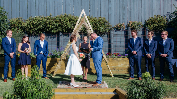 A Backyard Wedding in Auckland photographed my Mala Photography, an Auckland based wedding photographer. The bride and groom are standing in front of an arch in a backyard. Their attendants are standing beside them. The groom is emotional and wiping tears from his eyes.