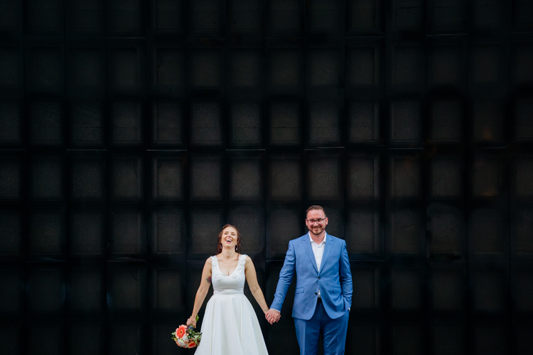 An Auckland CBD wedding photographed by an Auckland wedding photographer Mala Photography. This is a photo of a bride and groom standing in front of a black wall at Britomart. They are standing side by side,, holding hands and laughing.