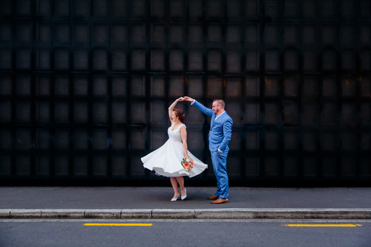 Photographed by an Auckland Wedding Photographer Mala Photography, this is a Bride and Groom dancing in front of a black wall at Britomart in Auckland's CBD. The groom is holding the bride hand while she spins around.