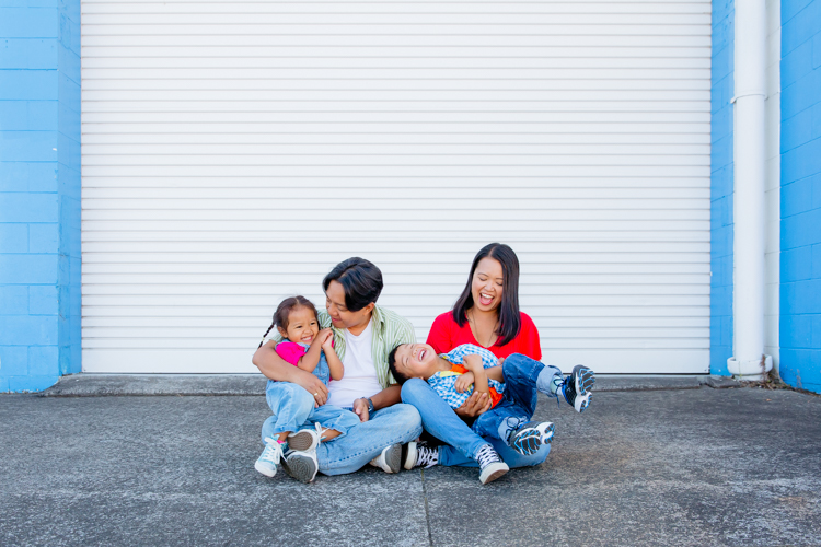 This is a family photo taken during a family portrait session by Mala Photography, and Auckland based photographer. This photo is of a family of four ie Mum, Dad and their son and daughter. They are playing with each other and having fun in front of a white roller door with bright blue brick work around it.
