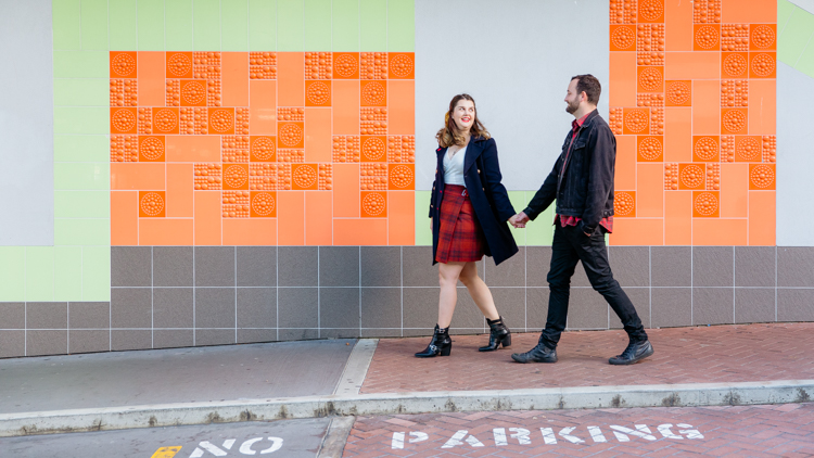 A photo from an inner city Auckland engagement shoot of a couple walking along holding hands and looking at each other. They are walking on a footpath with an orange, green and white tiled wall in the background. This photo was taken by Mala Photography. Mala is an Auckland based engagement and wedding photographer with a contemporary and creative style.