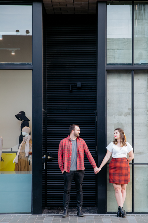 A photo from an inner city Auckland engagement shoot of a couple standing in a doorway. This photo was taken by Mala Photography. Mala is an Auckland based engagement and wedding photographer with a contemporary and creative style.