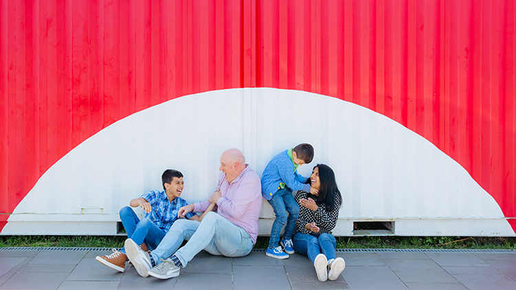 This is a family photo taken in Auckland by family portrait photographer Mala Photography. In this photo are a family of four - Mum, Dad and two young boys. They are sitting on the ground in front of a red and white shipping container at Wynyard Quarter. They are all smiling and laughing as the boys are tickling their parents.