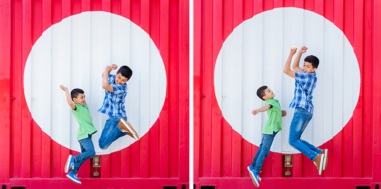 Taken during a family photo shoot in Auckland, this is a photo of two brothers jumping in the air and having fun. They are jumping in front of a bright red shipping container with a big red spot painted on it. This photo was taken during a family portrait session with Mala Photography, an Auckland based family portrait photographer.