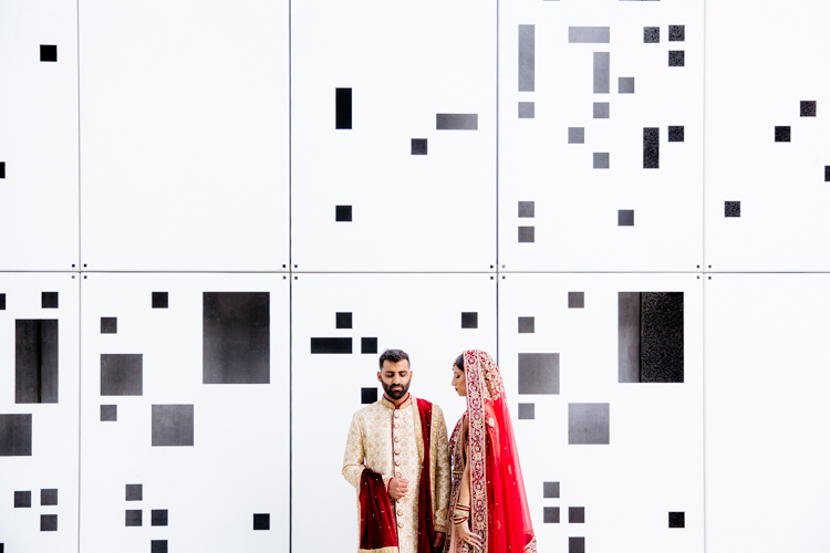 This is a photo from an Indian wedding in Auckland photographed by Mala Photography, and Auckland based wedding photographer that shoots Indian weddings throughout New Zealand. In this photo an Indian Bride and Groom are standing in front of a white wall with black geometric shapes on it.