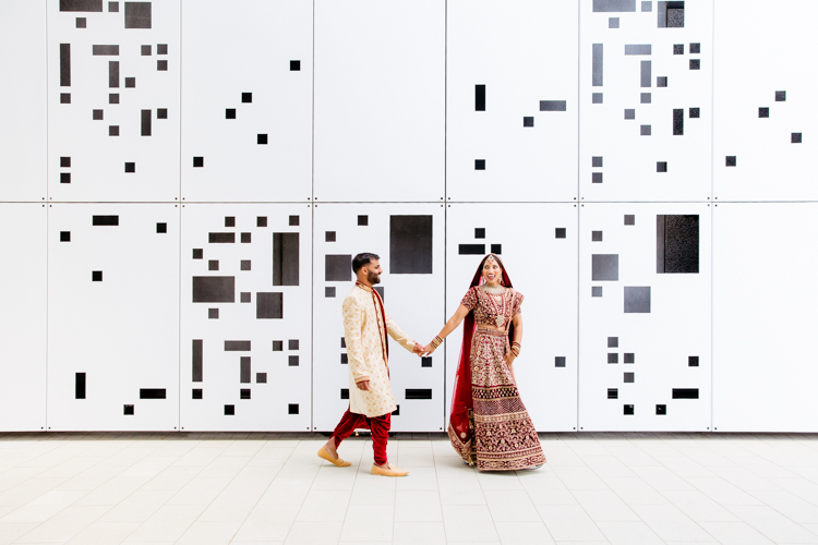 This is a photo from an Indian wedding in Auckland photographed by Mala Photography, and Auckland based wedding photographer that shoots Indian weddings throughout New Zealand. In this photo an Indian Bride and Groom are walking hand in hand in front of a white wall with black geometric shapes on it.