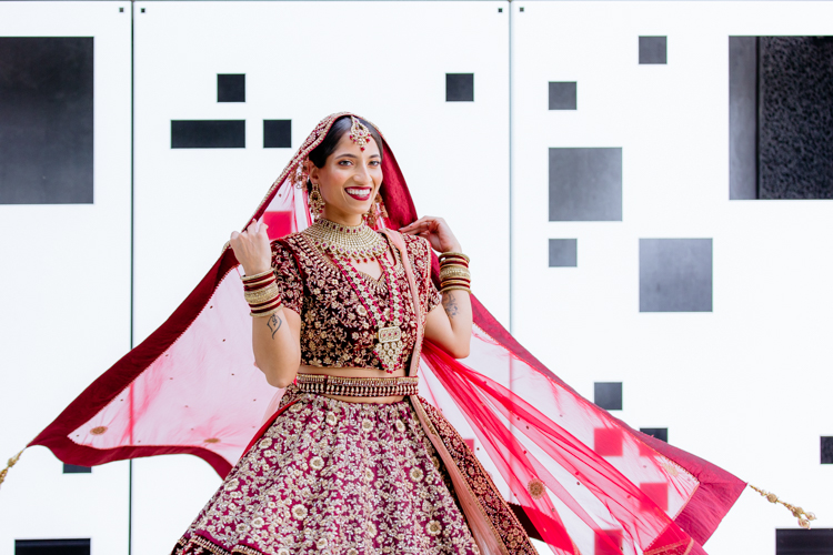 This is a photo from an Indian wedding in Auckland photographed by Mala Photography, and Auckland based wedding photographer that shoots Indian weddings throughout New Zealand. In this photo an Indian Bride dancing and spinning around in front of a white wall with black geometric shapes on it.