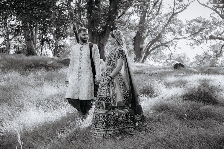 This is a wedding photo of an Indian Bride and Groom wearing traditional wedding outfits walking hand in hand in a park with tall trees around them. This wedding photo was taken by Mala Photography, an Auckland based wedding photography that specialises in photographing Indian weddings.