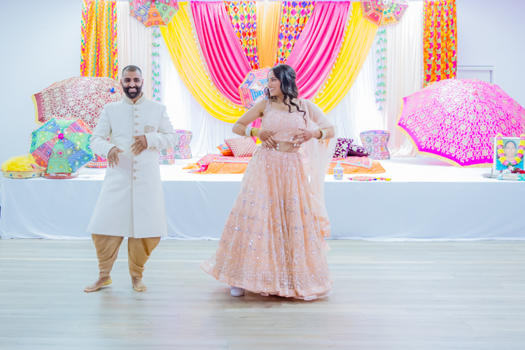 A photo of an Indian Bride and Groom dancing at their Sangeet. Photo taken by Mala Photography, an Auckland based photographer specialising in photographing Indian weddings.