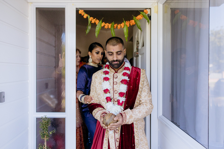 An Indian groom dressed in traditional Indian wedding attire leaving through the front door of his family home to attend his traditional Indian wedding. He has a garland of flowers around his neck and he's holding a coconut in his hands. His sister is walking behind him escorting him through the door. Photo taken by Mala Photography, an Auckland based Indian wedding photographer.