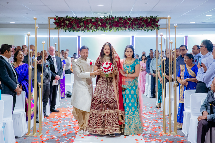 An Indian Bride arriving at her traditional Indian wedding escorted by her uncle and auntie. She is dressed traditionally in an Indian wedding outfit. Photo by Mala Photography. Mala has years of experience with Indian weddings in Auckland and around New Zealand.