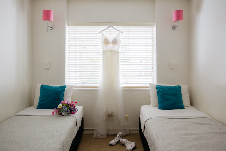 This is a photo of a white wedding dress hanging in a bedroom window. The Bride's wedding shoes, a pair of Chuck Taylor sneakers are on the floor in front of the dress. There are two beds in the room. One of them has the Bride's bouquet on it. Photo taken by Auckland wedding photographer Mala Photography.