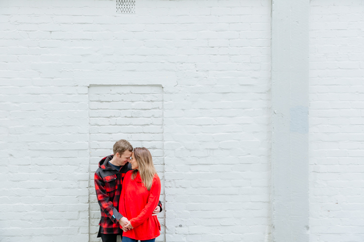 This is a photo of a newly engaged couple taken during their engagement shoot in Auckland. They are standing in front of a white brick wall in an alley way holding hands, looking at each other and smiling. They are dressed in bright red. This photo was taken by Mala Photography, an Auckland based wedding, engagement, portrait and event photographer.