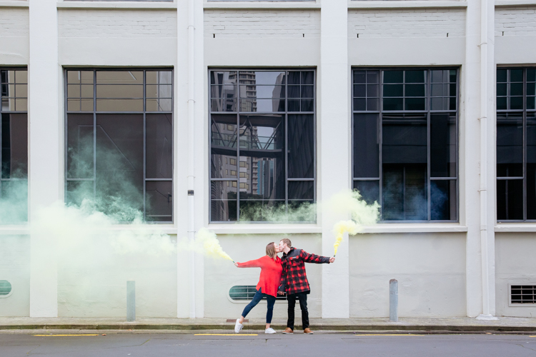 This is a photo of a newly engaged couple taken during their engagement shoot in Auckland. They are standing in front of a white building with big windows in an alley way holding hand, kissing and holding yellow smoke bombs. They are dressed in bright red. This photo was taken by Mala Photography, an Auckland based wedding, engagement, portrait and event photographer.